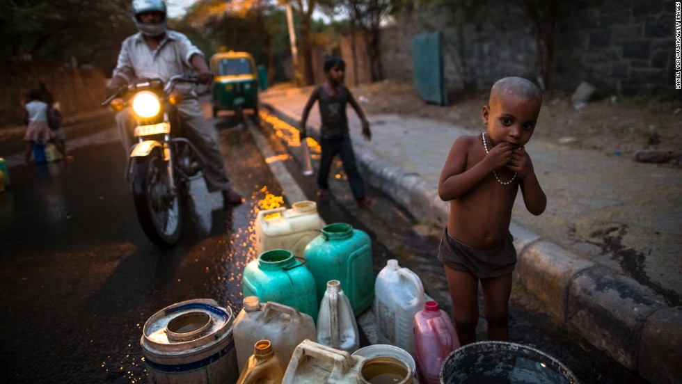 "MAY 23 - NEW DELHI, INDIA:  A boy minds his family's containers as people fill theirs with water. High temperatures are causing <a href=""http://cnn.com/video/data/2.0/video/world/2013/05/01/intv-india-drought-climate-change-sahgal.cnn.html"">a strain on water supplies in Delhi</a>, with many residents having to rely on water being brought in by trucks on a daily basis."
