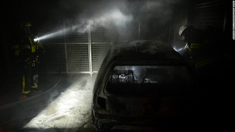 Firemen extinguish a burning car parked in an indoor garage in the Stockholm suburb of Tureberg on May 24.