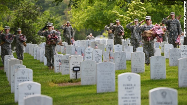 Members of the Third US Infantry Regiment, The Old Guard, salute as a funeral takes place in Section 60 of Arlington National Cemetery on May 23, 2013 in Arlington, Virginia. The soldiers were placing flags infront of graves ahead of Memorial Day. Memorial Day is in honor of those who died while serving in the armed forces of the US. AFP PHOTO/Mandel NGAN        (Photo credit should read MANDEL NGAN/AFP/Getty Images)