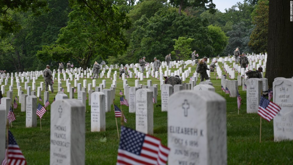 "Members of the Army's 3rd Infantry Regiment -- also known as the ""Old Guard"" -- plant flags at tombstones in Arlington National Cemetery in Washington on Thursday, May 23, ahead of Memorial Day. Washington is a city of war memorials."