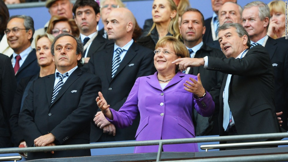 From left, UEFA President Michel Platini, German Chancellor Angela Merkel and German Football Association President Wolfgang Niersbach watch the action from the stands.