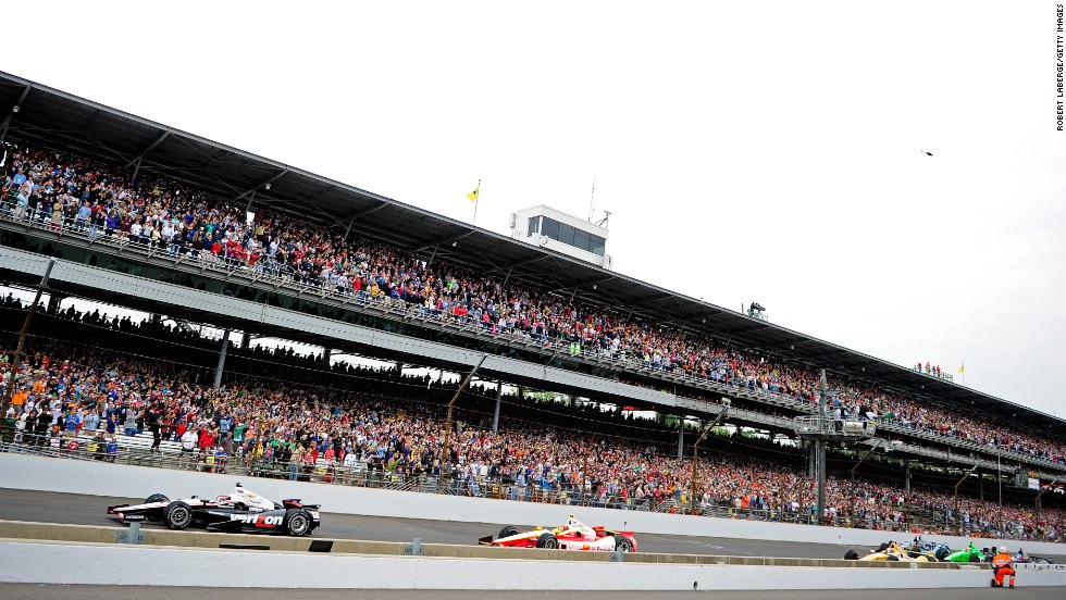 Will Power of Australia in No. 12 leads cars down the front stretch.