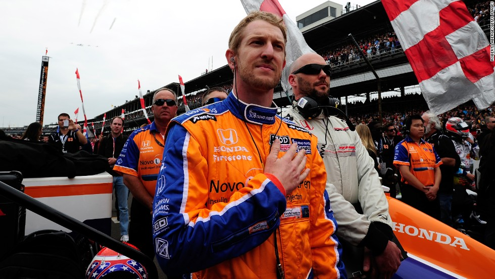 Driver Charlie Kimball stands on the grid during the performance of the national anthem.
