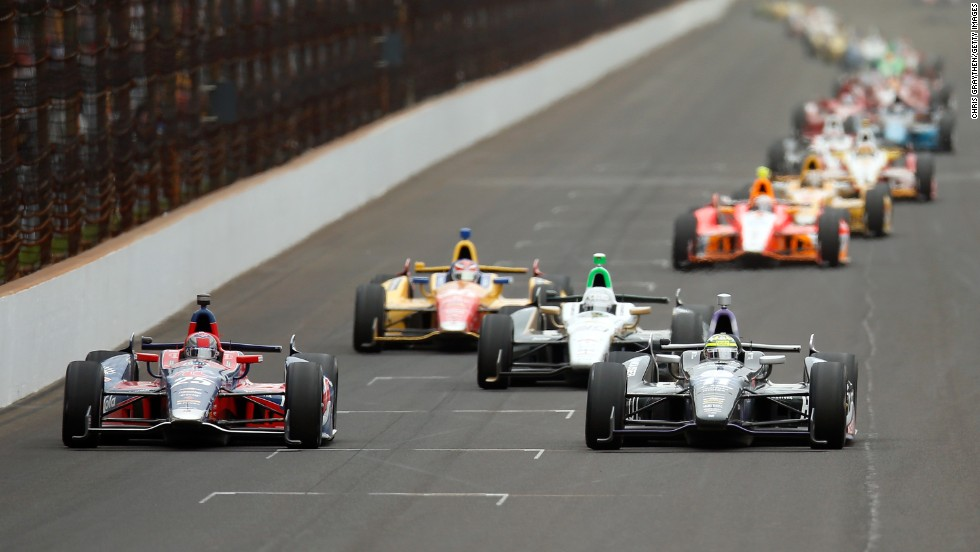 Marco Andretti in No. 25 for Andretti Autosport, left, and Tony Kanaan of Brazil in No. 11 lead the pack before a turn.