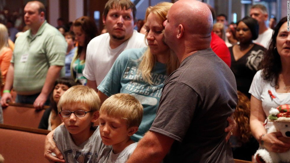 Tornado victims Christa and Russell Smith hug their children, Evan and Justin Smith, as the service takes place.