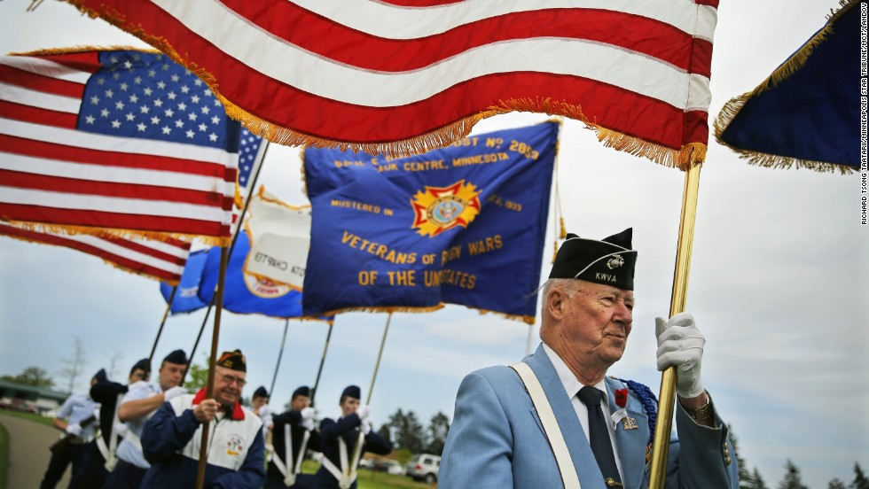 Korean War veteran Bob Pellow, 84, carries a flag during the ceremony at the State Veterans Cemetery near Little Falls on May 26.