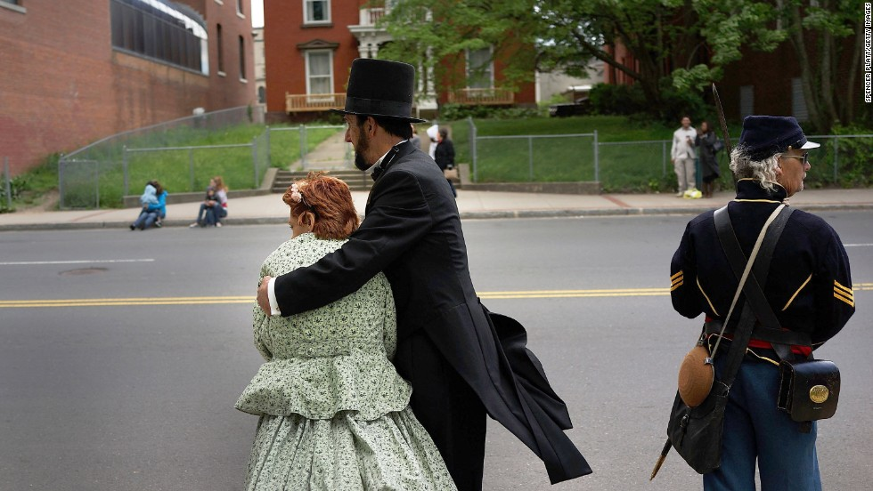 A couple dressed as Abraham and Mary Todd Lincoln embrace while waiting for the Memorial Day parade in Waterbury to pass on May 26.