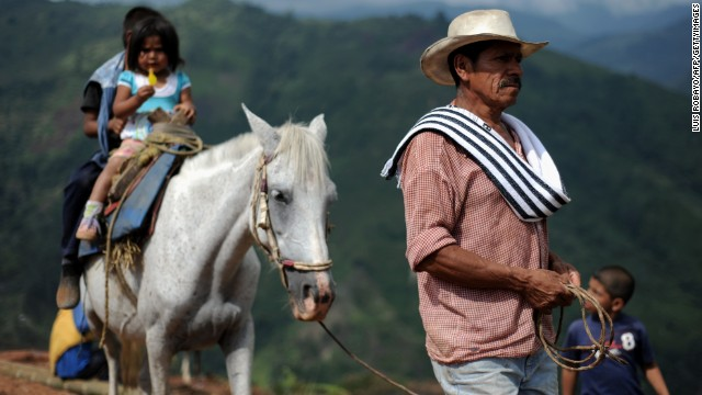 A farmer leads his horse with his children mounted on it on a hill in Calandaima, rural area of Miranda, department of Cauca, Colombia, on June 28, 2012.