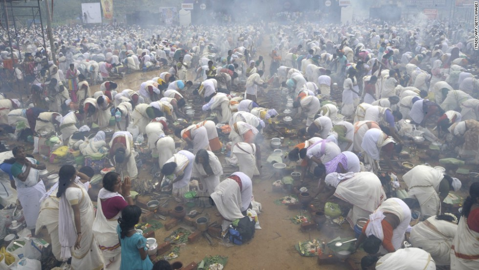 Hindu devotees pray and prepare rice porridge in the streets surrounding the Attukal Bhagavathy Temple in Thiruvananthapuram on March 7, 2012 as they take part in the Pongala Festival in Kerala. More than 3.5 million women took part in the festival, attempting to set a world record for the largest gathering of women at a festival.