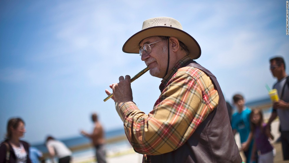 Bob Harty plays the flute on the boardwalk in Seaside Heights, which is mostly reopened to the public.