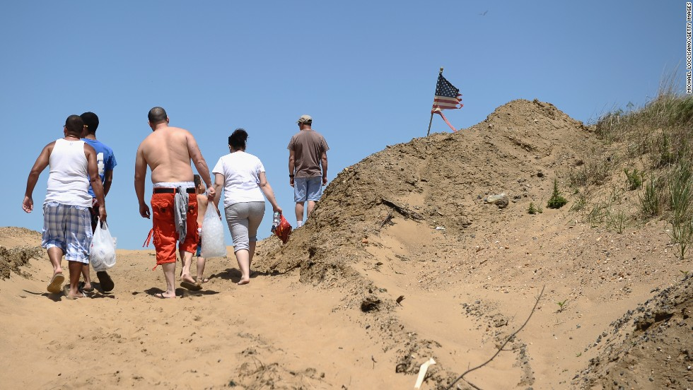 Beachgoers walk up a dune on Memorial Day in Keansburg, which was devastated by Sandy.