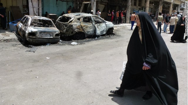 An Iraqi woman walks past burnt out vehicles and damaged buildings following a car bomb that exploded the previous day in the commercial centre of the capital Baghdad on May 28, 2013. Violence in Iraq has killed more than 500 people in May, AFP figures showed, as authorities struggled to contain a wave of unrest that has raised fears of new sectarian conflict. AFP PHOTO / SABAH ARAR (Photo credit should read SABAH ARAR/AFP/Getty Images)