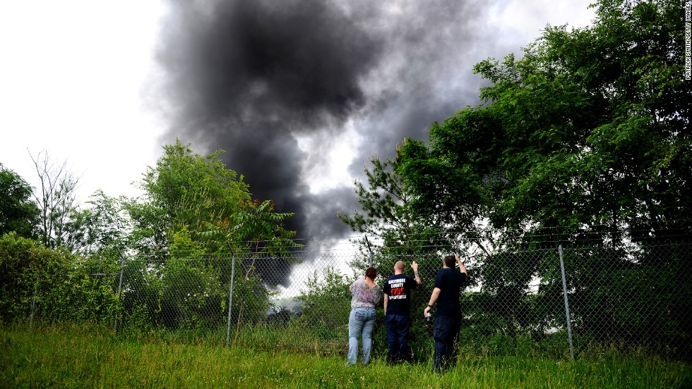 Onlookers watch the event unfold as black smoke billows into the sky.