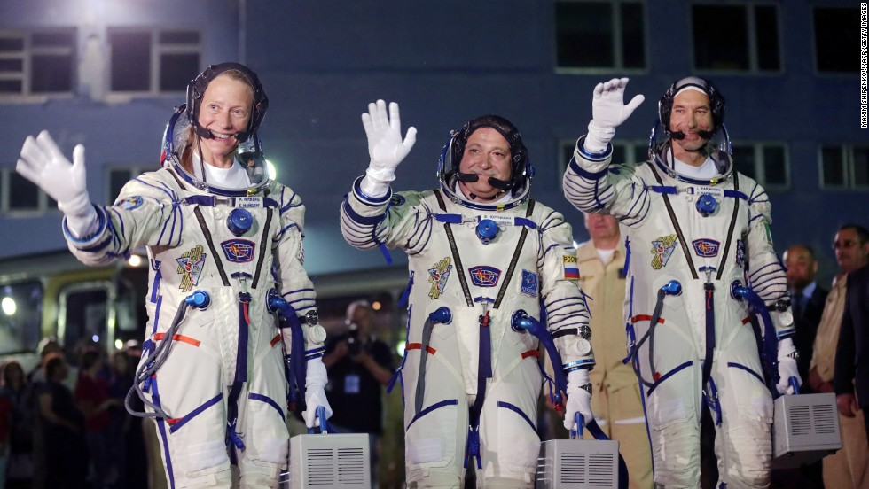 The astronauts wave to a crowd outside their hotel on May 28.