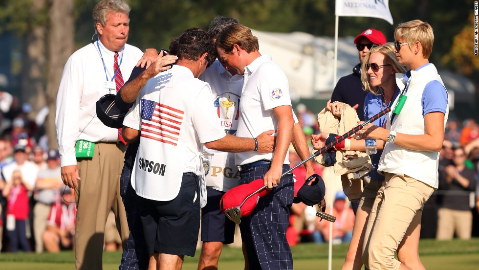 Watson, Webb Simpson and their caddies pray during the 39th Ryder Cup at Medinah, Illinois. They were later met by their wives, who also joined in the huddle.