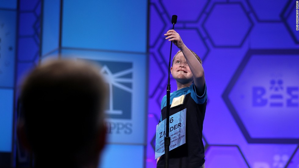 "Zander Reed of Ankeny, Iowa, reaches to adjust the microphone before spelling ""blottesque"" in the third round on May 29. Blottesque means to be painted with blot-like brushwork."