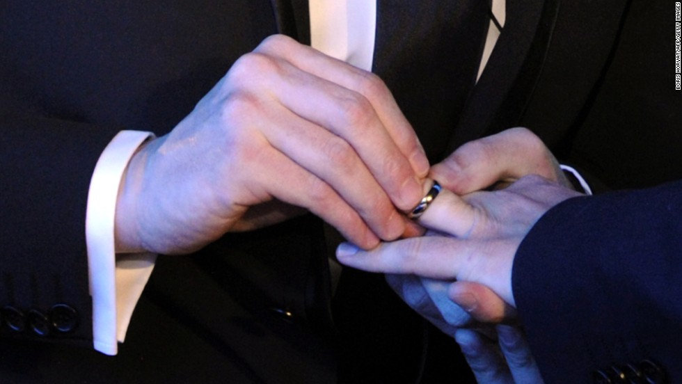 a same sex couple exchange wedding rings at their marriage ceremony