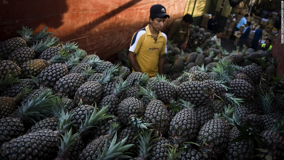 A vendor sells pineapples at the wholesale fruit market in Lima.