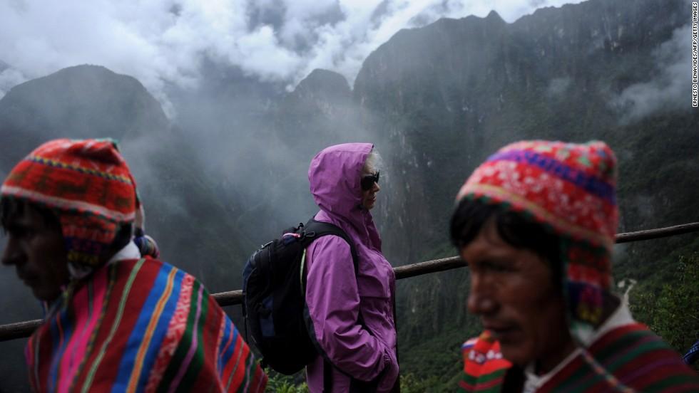 A foreign tourist, center, arrives at Machu Picchu in Cusco.