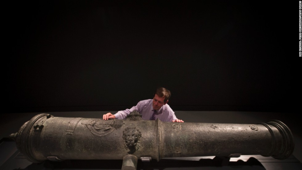 Maintenance Coordinator Brian Robinson poses next to a cannon recovered from the wreck.
