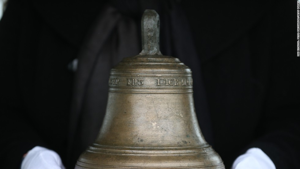 Conservator Susan Bickerton holds the original ship's bell at the location of it's 16th Century sinking.