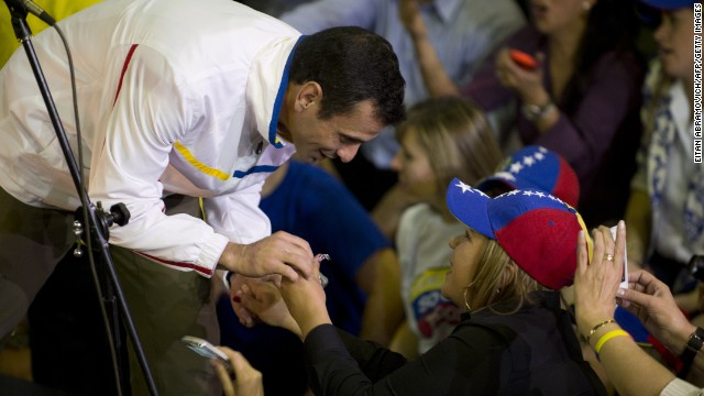 "Venezuelan opposition leader Henrique Capriles (L) is greeted by Venezuelans residing in Colombia, during a meeting in Bogota, on May 30, 2013. Capriles denounced as ""blackmail"" a threat by Caracas to end support for talks to end Colombia's civil war over his visit with Colombia's president."