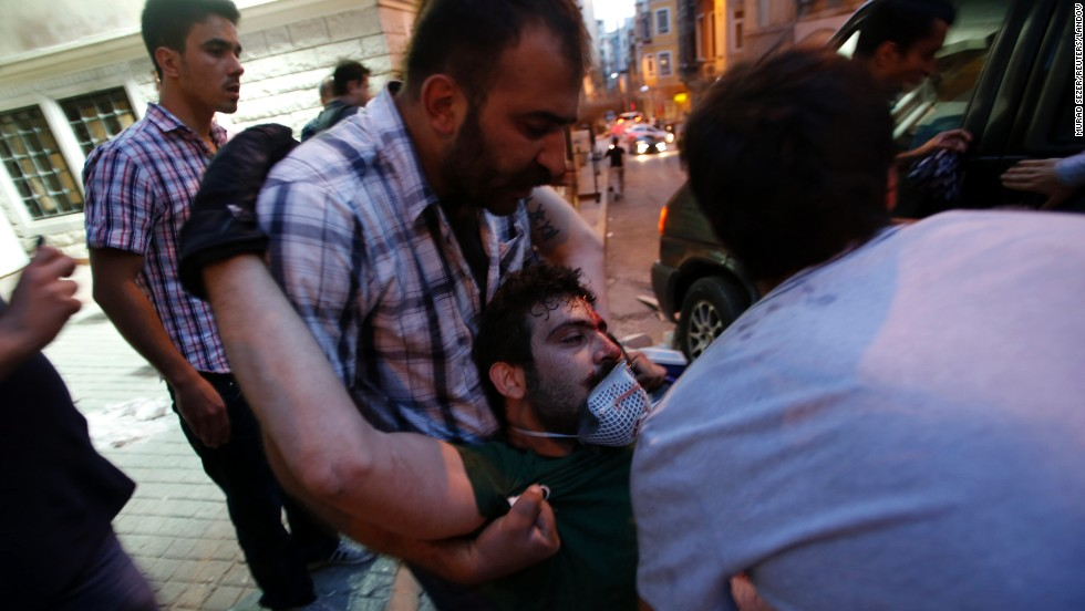 Friends carry an injured protester on May 31. More than a dozen people have been injured in the clashes.