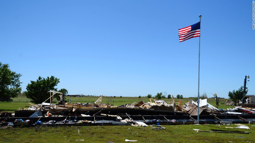 An American flag flies above the destroyed remains of a mobile home in El Reno on June 1.