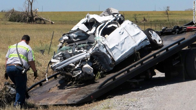 The wreckage of a vehicle used by storm chasers is loaded onto a flatbed truck at the intersection of 10th and Radio in Canadian County, near El Reno, Oklahoma on Sunday, June 02, 2013.  Storm chasers Tim and Paul Samaras and Carl Young were killed chasing a tornado on Friday night.  The intersection is being guarded by a sheriffís deputy.  The chasers were among nine people killed in storms that struck Oklahoma on Friday night.