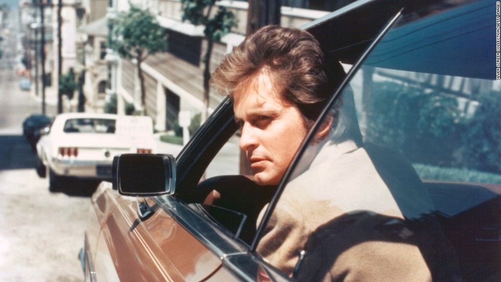 "Douglas peers out of the window of a car as Inspector Steve Keller on ""Streets of San Francisco."""