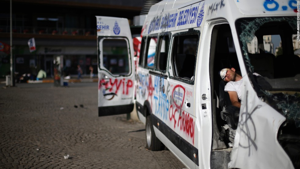 After protests that lasted until the early morning, a protester sleeps in a damaged and vandalized vehicle in Taksim Square on June 3. Protests showed no sign of letting up on Monday, almost a week after a peaceful sit-in was met with a police crackdown, igniting the biggest anti-government riots the city has seen in a decade.