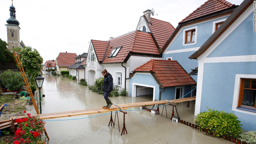 A women crosses a makeshift bridge over flooded streets in Unterloiben, Austria, on Tuesday, June 4.