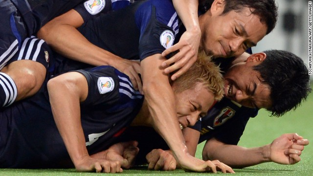 Japan's Keisuke Honda is mobbed by his teammates after scoring a 91st-minute penalty.