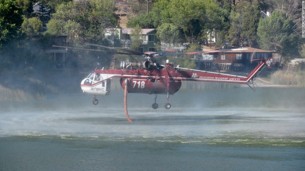 A helicopter fills up from Lake Hughes to battle the Powerhouse wildfire on June 3 in Palmdale.