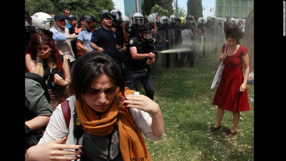 "Turkish riot police spray a woman in Taksim Square with pepper spray on May 28, 2013. The <a href=""http://www.cnn.com/2013/06/05/world/meast/turkey-woman-in-red/index.html"">woman in a red dress</a> became an icon of the violent protests in Turkey, making international headlines and spreading across social media."