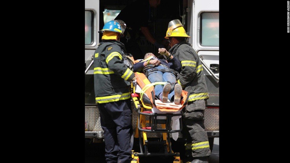 Emergency personnel load an injured person into an ambulance.