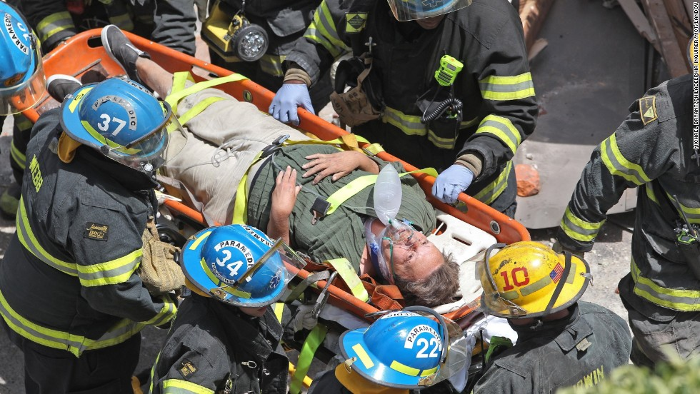 Firefighters carry a survivor from the rubble.