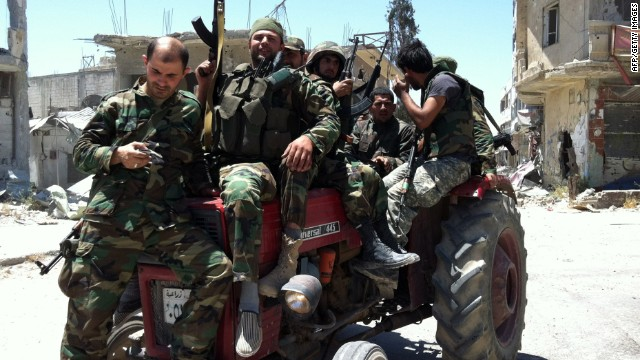 Syrian army's soldiers sit on a tractor holding their weapons on June 5, 2013 in the city of Qusayr in Syria's central Homs province, after the Syrian government forces seized total control of the city and the surrounding region.
