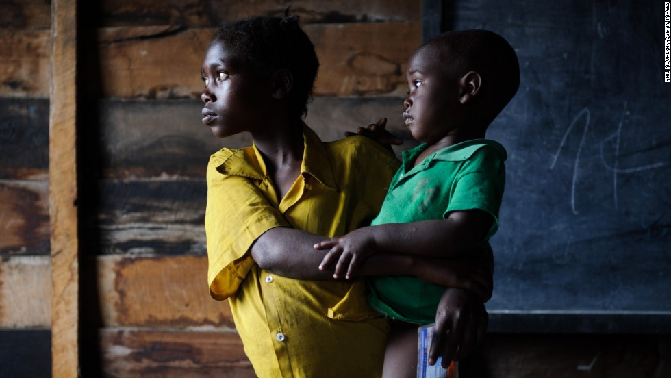A displaced Congolese girl holds a child in a classroom used for shelter in the village of Kibati, on the outskirts of Goma.