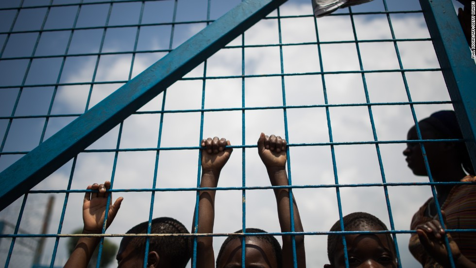 Displaced children stand against the gate of a religious organization on the outskirts of Goma.