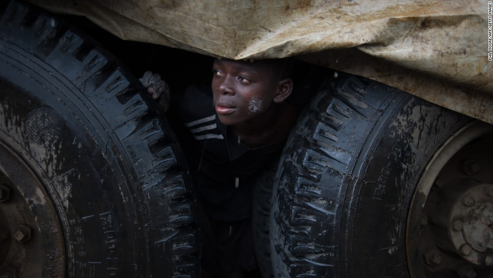 An internally displaced Congolese boy shelters from the rain under a truck in the Mugunga III camp.