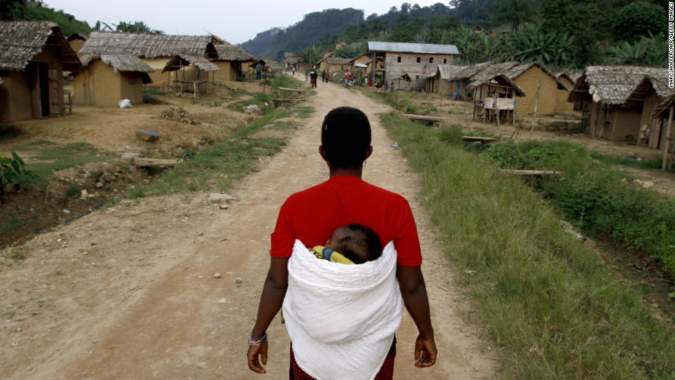 A woman walks with her child down the main road in the village of Luvungi.