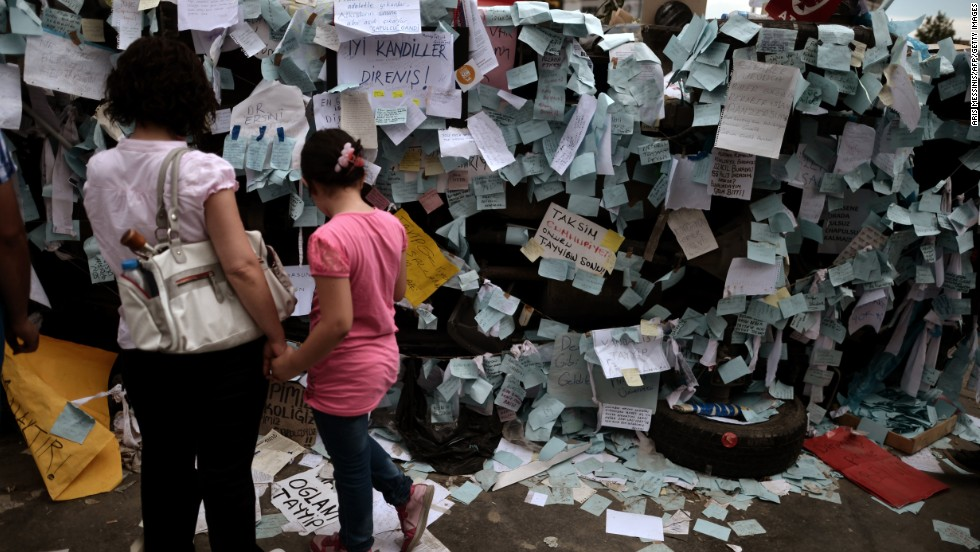 A mother and her daughter read notes placed by protestors on a destroyed car in Taksim Square on June 6. Thousands of striking union members joined the anti-government protests on June 5, marching in Istanbul and Ankara in a sea of red and white union flags, drumming and yelling for Prime Minister Recep Tayyip Erdogan to resign.