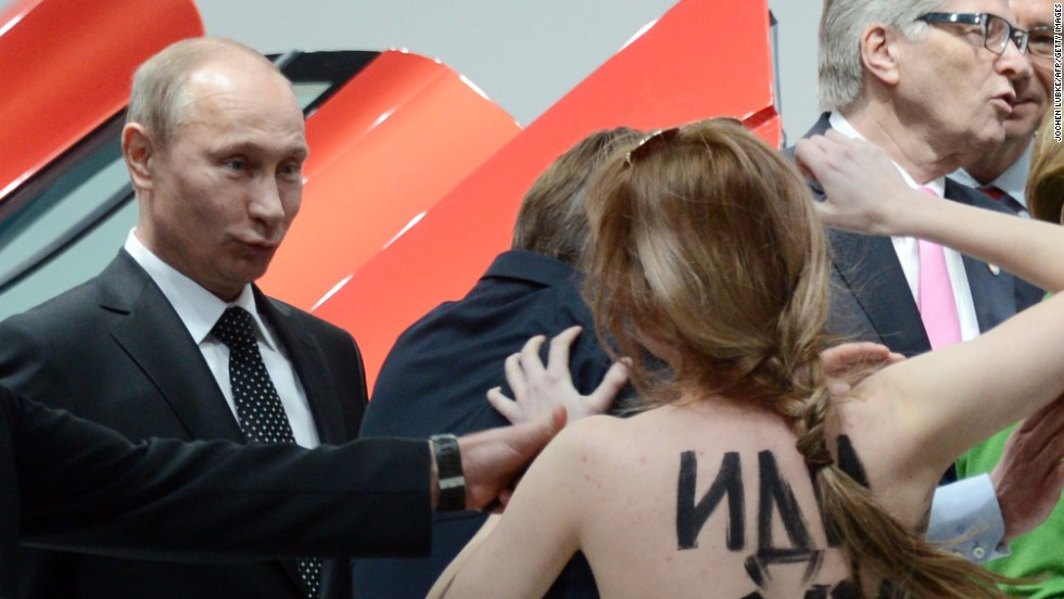 A topless protester shouts at Putin and German Chancellor Angela Merkel during a visit to the Hanover Industrial Fair in central Germany in April 2013. Human rights groups say civil liberties and democratic freedoms have suffered during Putin's rule.