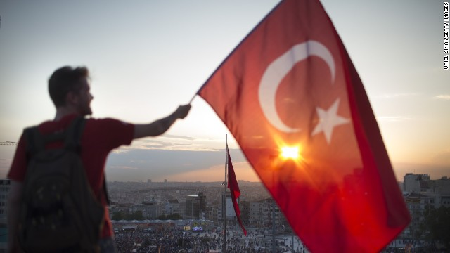 ISTANBUL, TURKEY - JUNE 03: A protestor waves the Turkish flag from a roof top at Taksim square on June 3, 2013 in Istanbul, Turkey. The protests began initially over the fate of Taksim Gezi Park, one of the last significant green spaces in the center of the city. The heavy-handed viewed response of the police, Prime Minister Recep Tayyip Erdogan and his government's increasingly authoritarian agenda has broadened the rage of the clashes. (Photo by Uriel Sinai/Getty Images)Ê