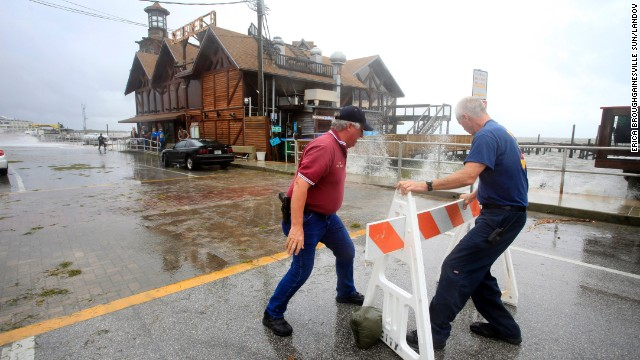 Cedar Key Police Chief Virgil Sandlin, left, and Fire Chief Robert Robinson set up roadblocks to prevent drivers from passing the flooded streets as Tropical Storm Andrea makes landfall in Cedar Key, Florida, on Thursday, June 6.
