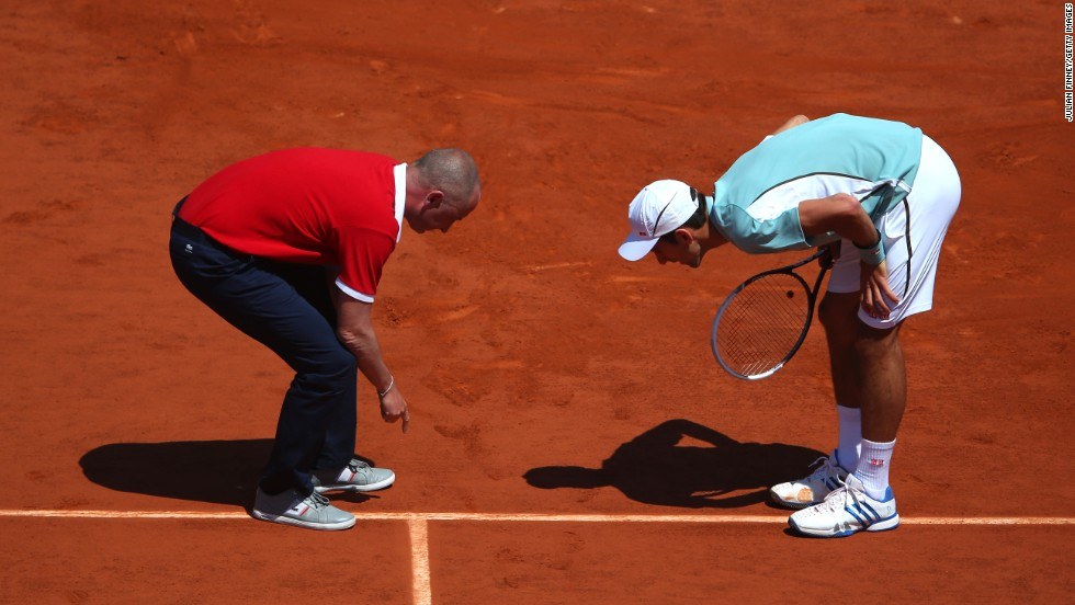 Umpire Pascal Maria checks a line call with Djokovic on June 7.