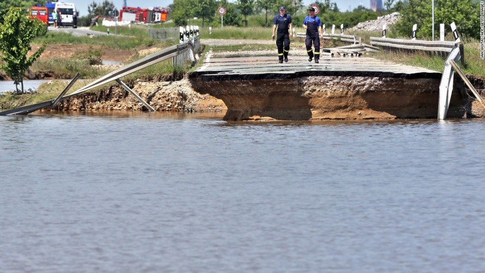 Members of the emergency services inspect a road washed away by flood water near Loebnitz, eastern Germany, on June 7.