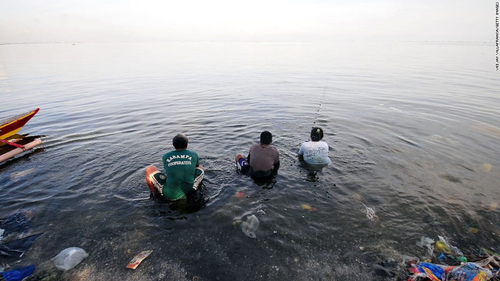 JUNE 7 - MANILA, PHILIPPINES: Fishermen cast their nets on the shallow end of polluted Manila Bay. This Filipino community is considered to be amongst the poorest in the country. With Manila's fishing exploited by commercial fishers, the fisher folk are struggling to earn a living from their trade.