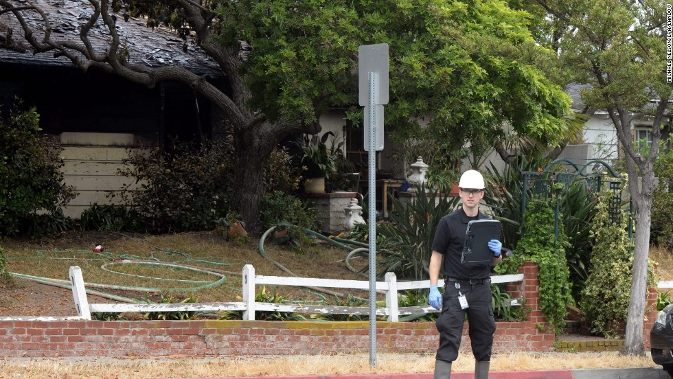 An inspector stands outside the partially burnt house where two bodies were discovered near the Santa Monica College campus.